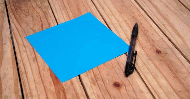 Blank blue paper for quotes with pen on top wood table Premium Photo