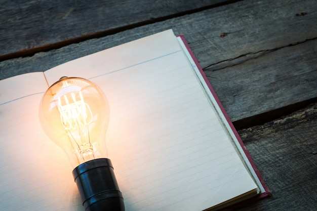 Blank book with a lit lightbulb on top Free Photo