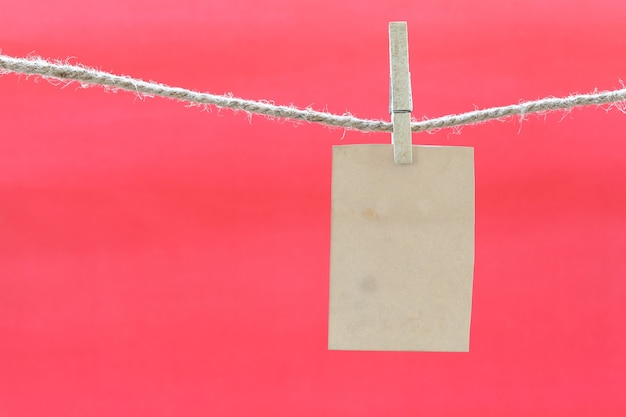 Blank brown note on clothesline and red background. Premium Photo