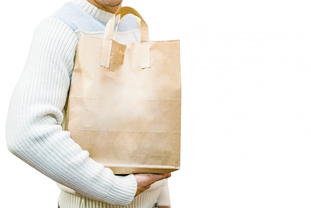 Blank brown paper bag with handles in men's hand in a white sweater isolated on a white Premium Photo