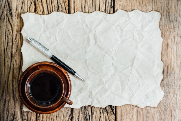 Blank burned paper with pen and coffee cup on old wood table. Premium Photo