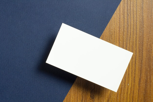 Blank business cards half of each lie down on blue textured  paper and wooden desk Free Photo