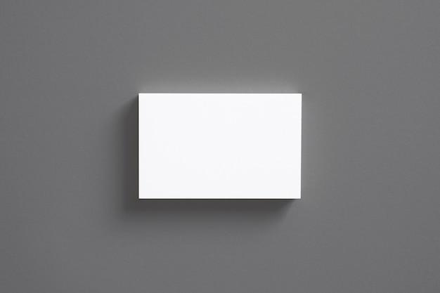 Pila di biglietti da visita in bianco isolata sulla vista superiore grigia Foto Gratuite