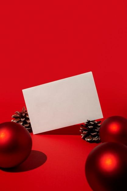빈 카드와 빨간색 크리스마스 볼과 빨간색 테이블에 소나무 콘 무료 사진