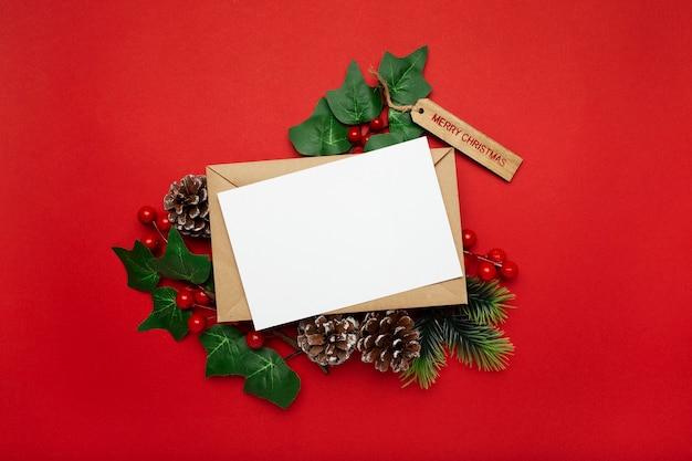 赤いテーブルにヤドリギと松ぼっくりの空白のカード 無料写真