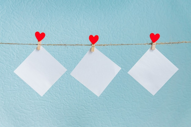 Blank cards on pins with red hearts. mockup for text and blue background for valentines day greetings Premium Photo