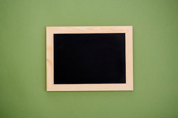 緑の背景に分離された木製フレームで空の黒板。デザインのモックアップ。 Premium写真