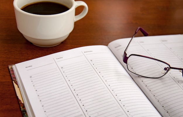 Blank checklist on wooden table with coffee and glasses Premium Photo