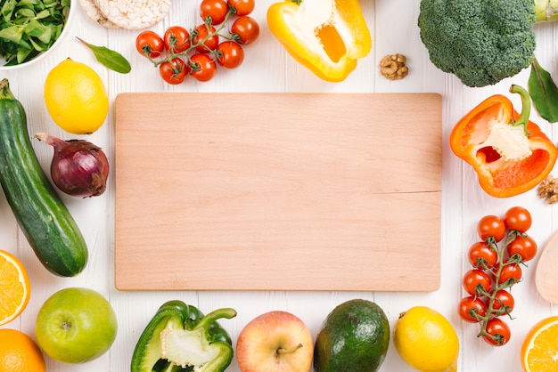 Blank chopping board surrounded with colorful vegetables and fruits on white table Free Photo