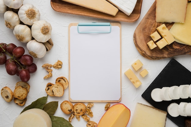 Blank clipboard surrounded by delicious ingredient over plain background Free Photo