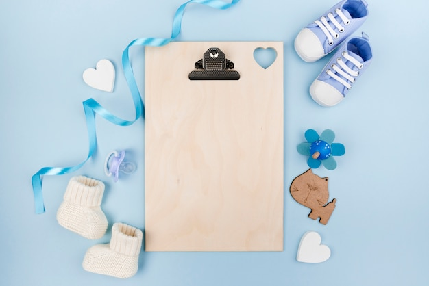 Blank clipboard with baby shoes Free Photo