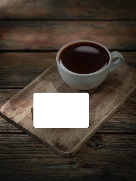 Пустая кредитная карта с чашкой кофе на деревянном столе Premium Фотографии