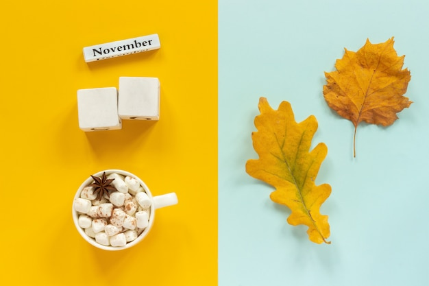 Blank cubes mockup and november for your calendar data, cup of cocoa and yellow autumn leaves Premium Photo