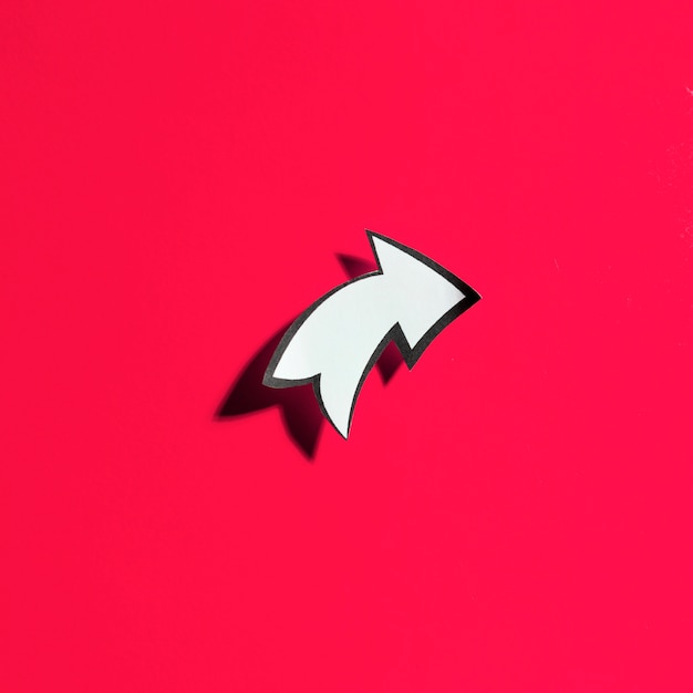 Blank cut out white directional arrow with black border on red background Free Photo