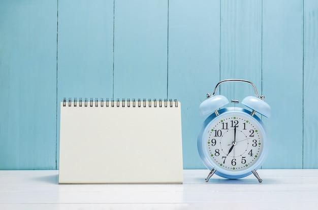 Blank desk calender with vintage alarm clock Premium Photo