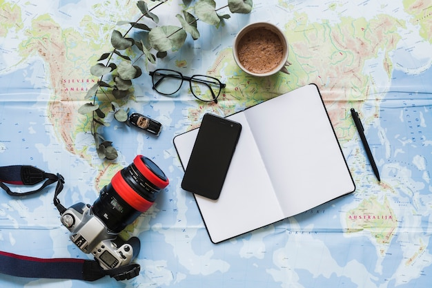 Blank diary, personal accessories, and coffee cup on the world map Free Photo