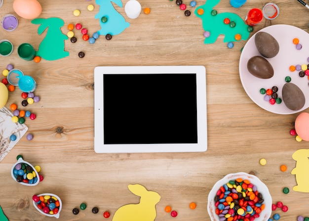 Blank digital tablet surrounded with colorful gems candies; easter eggs; paper cutout bunny on wooden table Free Photo