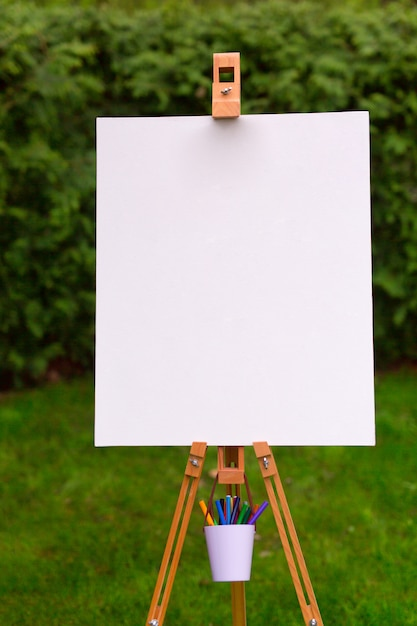 Blank easel template in the garden background Premium Photo