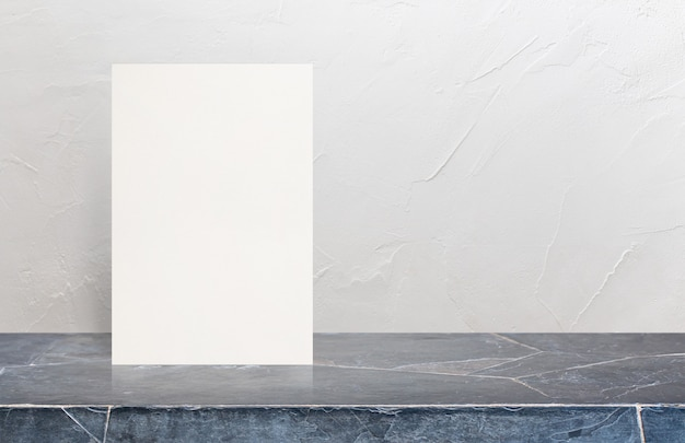 Blank eco textured paper poster on marble stone table top at white wall background. Premium Photo