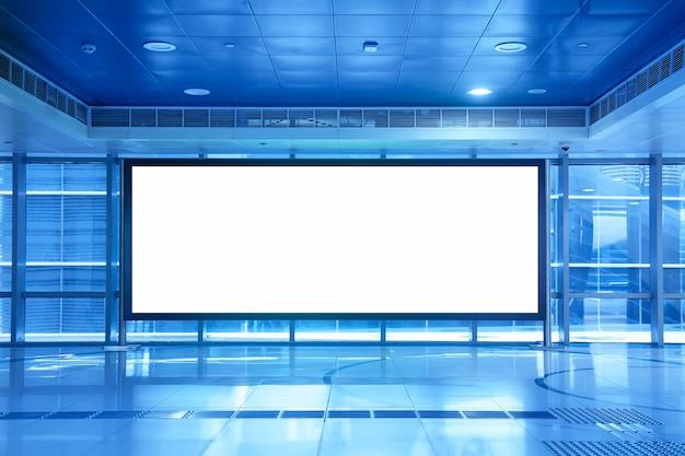 Blank empty billboard inside a shopping mall or metro underground in dubai, uae. blue toned Premium Photo
