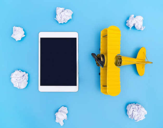 Blank empty tablet with yellow plane on blue and white cloud paper sky for travel concept Premium Photo