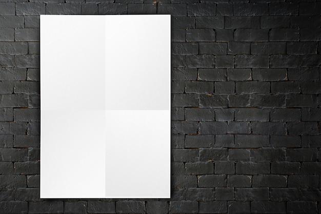 Blank folded paper poster hanging on black brick wall Premium Photo