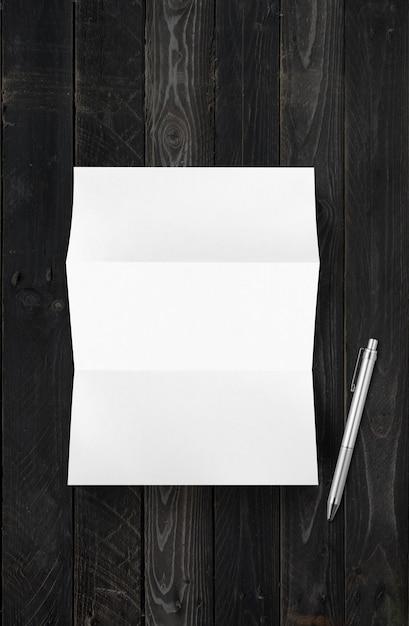 빈 접힌 흰색 A4 종이 시트 모형 및 펜 검은 나무 배경에 고립 프리미엄 사진