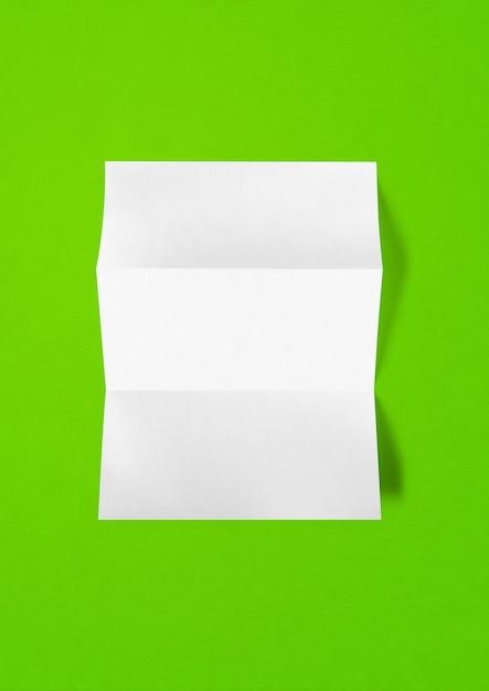 녹색 배경에 고립 된 빈 접힌 흰색 A4 종이 시트 모형 템플릿 프리미엄 사진