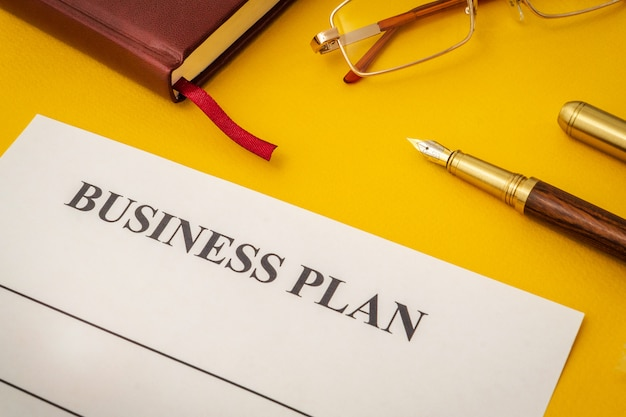 Blank form, glasses and pen for drawing up business plan on yellow table Premium Photo