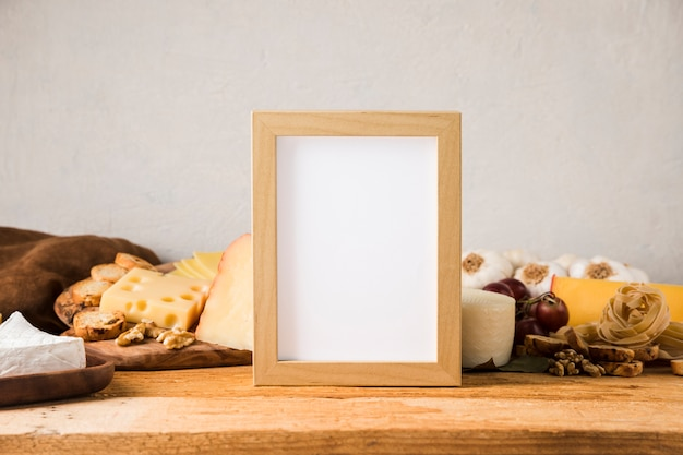Blank frame in front of cheese and ingredient on wooden table Free Photo