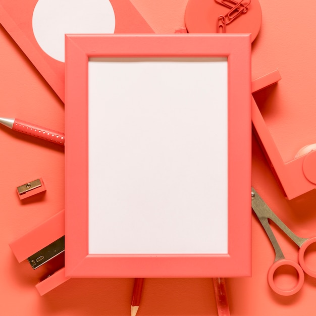 Blank frame and pink stationery on colored surface Free Photo