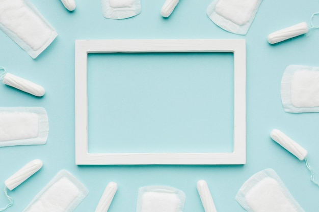 Blank frame surrounded by feminine products Premium Photo