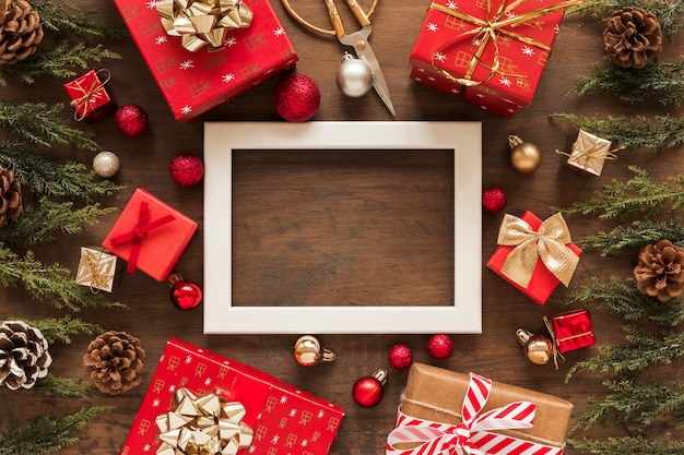 Blank frame with bright gifts on table Free Photo