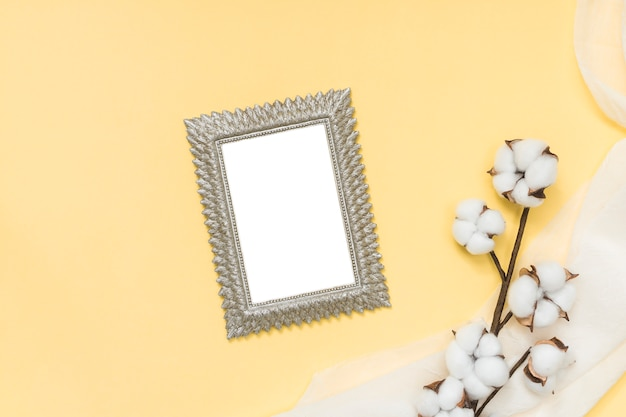 Blank frame with cotton branch on yellow table Free Photo