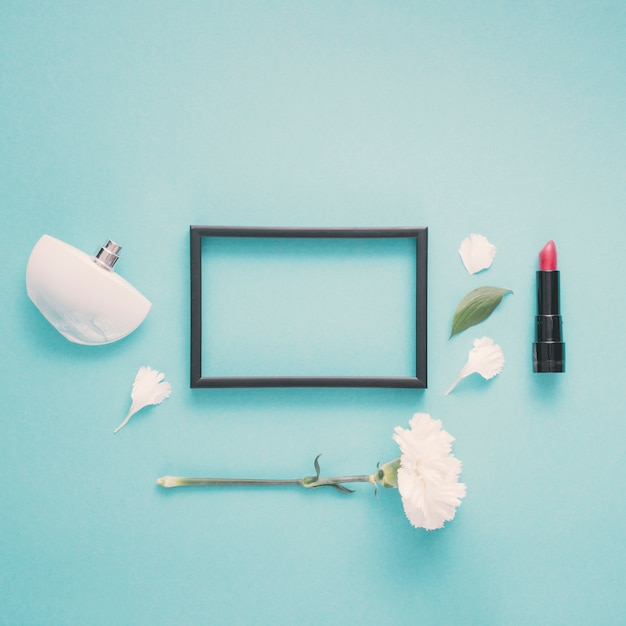 Blank frame with lipstick and flower on table Free Photo