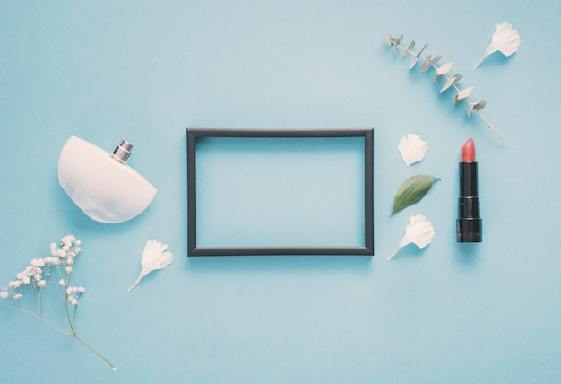 Blank frame with lipstick and plants on table Free Photo