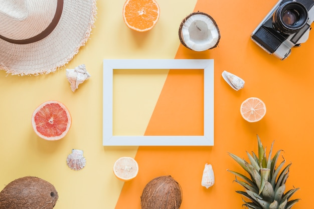 Blank frame with travel accessories, fruits and shells Free Photo