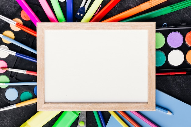 Blank framed paper arranged over colorful drawing tools on chalkboard Free Photo