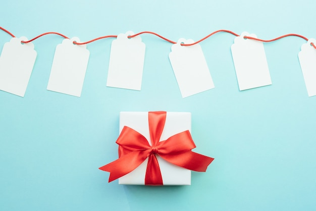 Blank gift tags mock-ups with red ribbon and gift box with bow on blue background. discount or sale concept. Premium Photo
