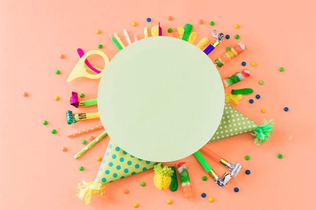 Blank green frame over party accessories and candies on orange backdrop Free Photo