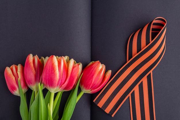 Пустая открытка на 9 мая. красные цветы, георгиевская лента на черном блокноте. день победы или день защитника отечества концепции. вид сверху, скопируйте пространство для текста Premium Фотографии