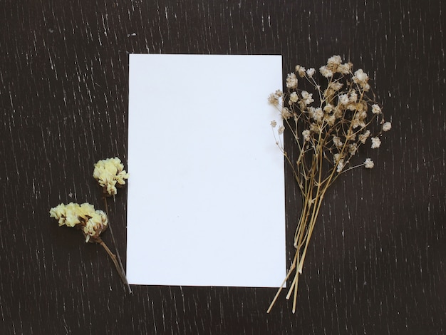 Blank greeting card with flower on rustic wood background for creative work design Free Photo