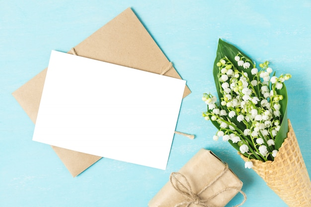 Blank greeting card with spring lily of the valley flowers in waffle cone with gift box on blue background. mock up. flat lay Premium Photo