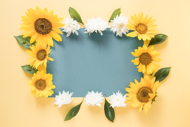 Blank grey paper surrounded with flowers over yellow background Premium Photo