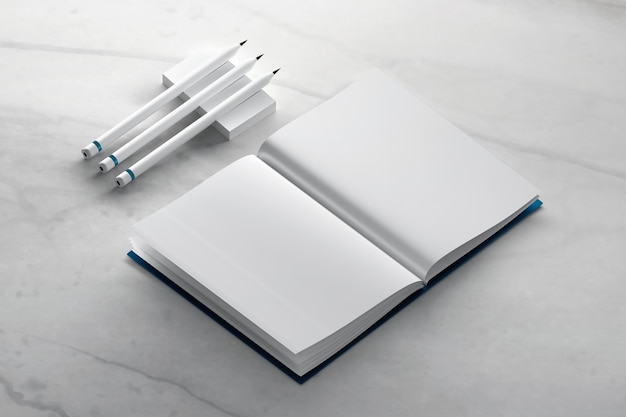 Blank journal book mockup with pencils on marble surface Premium Photo