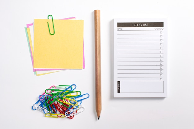 Blank to do list planner with checklist, wooden pencil, colorful paper clips and note papers isolated on white background. Free Photo