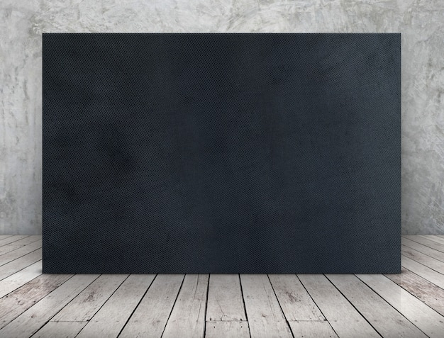 Blank long black fabric canvas frame leaning at concrete wall on wooden plank floor Premium Photo