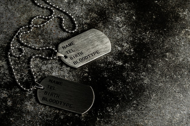 Blank military dog tags on abandoned rusty metal plate. Premium Photo