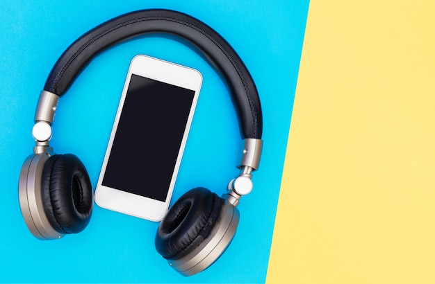 Blank mobile phone screen inside of golden headphone Premium Photo