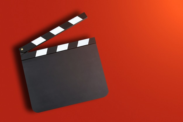 Blank movie production clapper board over red background with co Premium Photo
